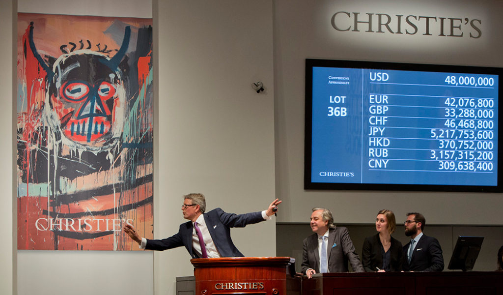 """Christie's Global President Jussi Pylkkanen takes bids on Jean-Michel Basquiat's """"Untitled"""" (1982) at the Post-War & Contemporary Art Evening Auction in NYC, fetching a record $57,285,000. (© Christie's Images LTD. 2016)"""