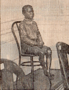 a life-size terra cotta sculpture of a boy seated on an art deco chair.