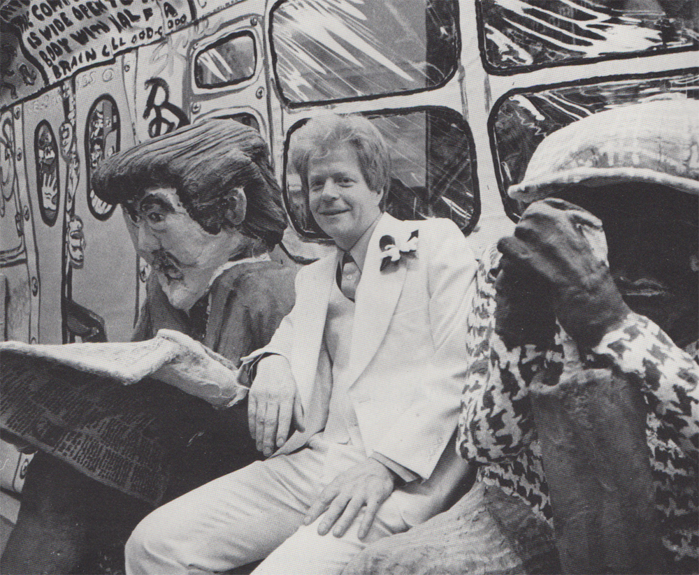 "Red Grooms seated between passengers on his ""Subway"" at the May 1976 opening of ""Ruckus Manhattan"". Photograph by John Cornell; ©1976 Newsday Inc."